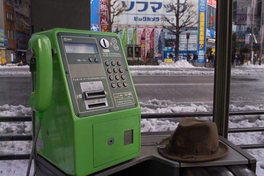 公衆電話と帽子
